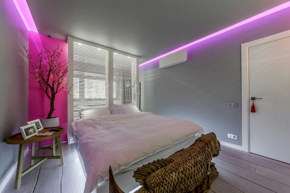 Розовая подсветка серой стены в спальне