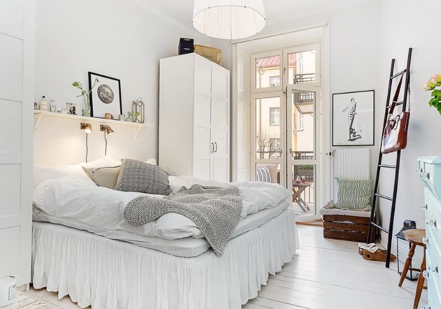 Белая полка над кроватью в спальне скандинавского стиля