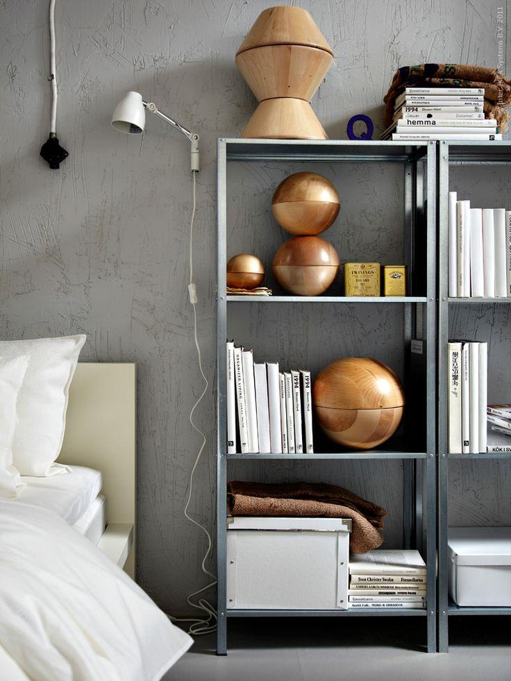Серый металлический стеллаж около кровати