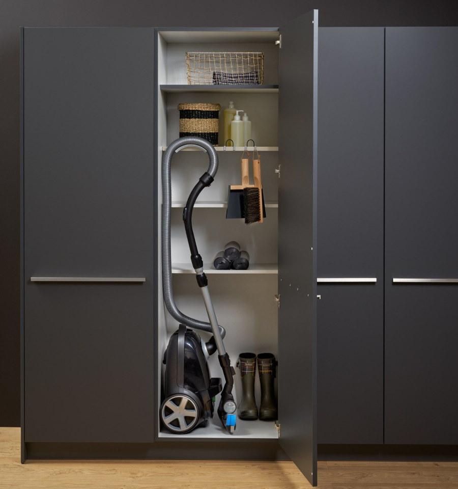 Пылесос и щетки внутри серого шкафа в прихожей