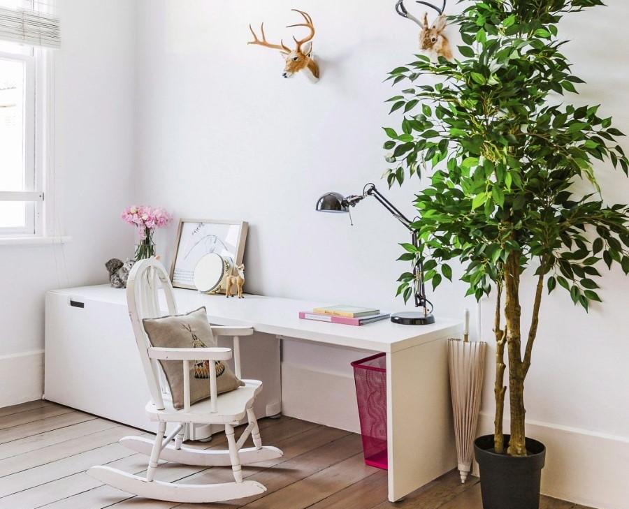 Детский столик за крупным растением в кадке