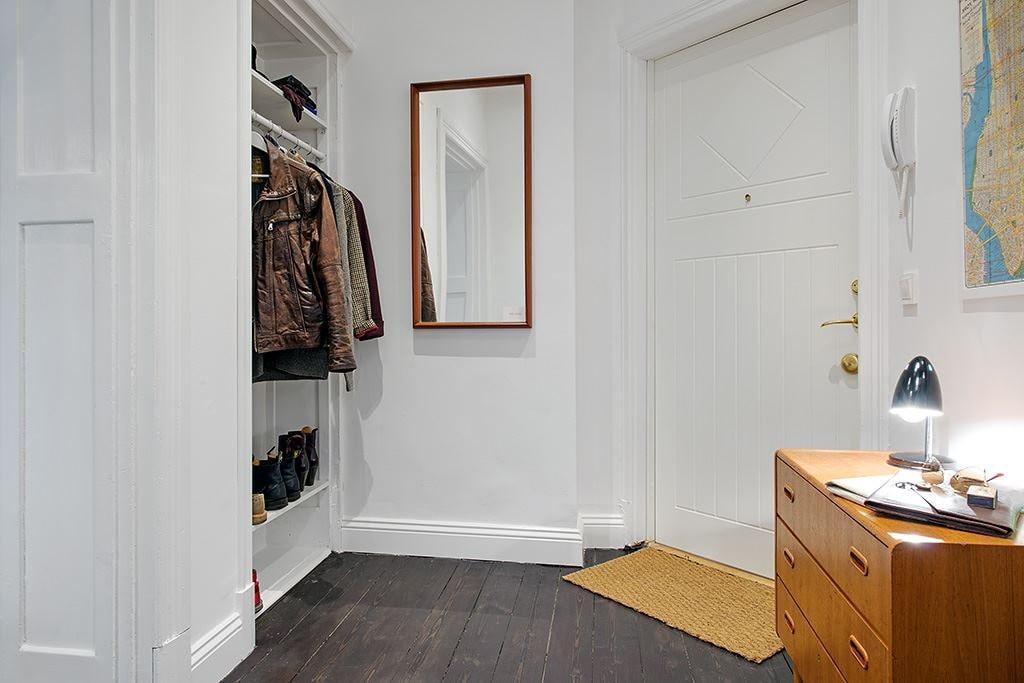 Верхняя одежда на вешалках в гардеробе около двери