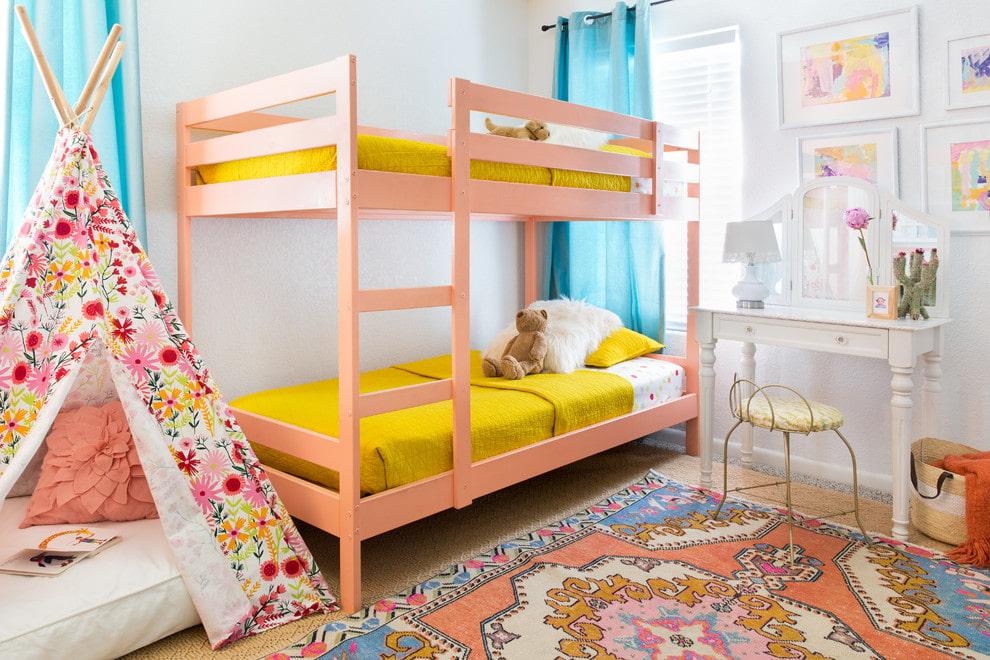 Розовая кровать из дерева в комнате сестер