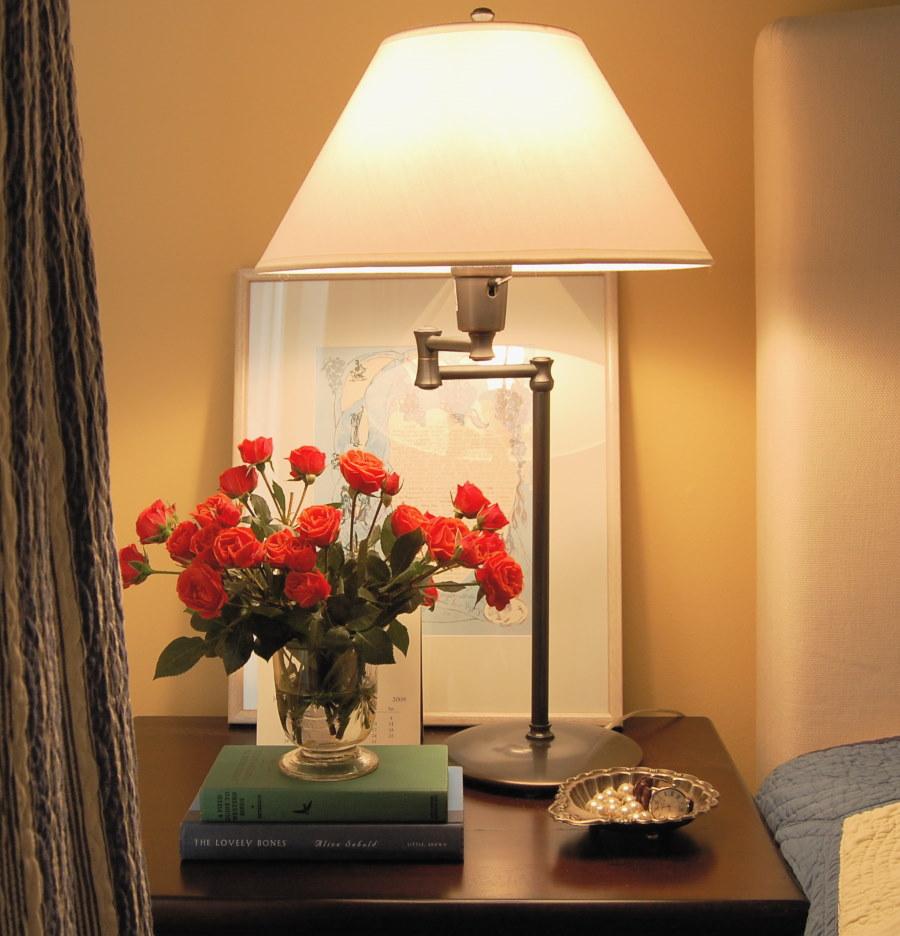 Красные розы под настольной лампой в спальне