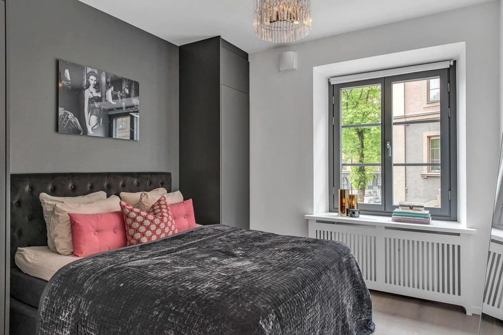 Розовые подушки в серой спальне хрущевки