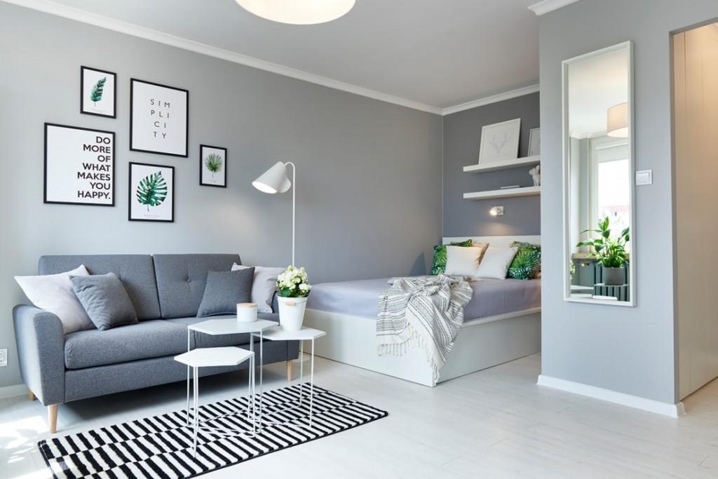 Кровать около дивана в серой комнате