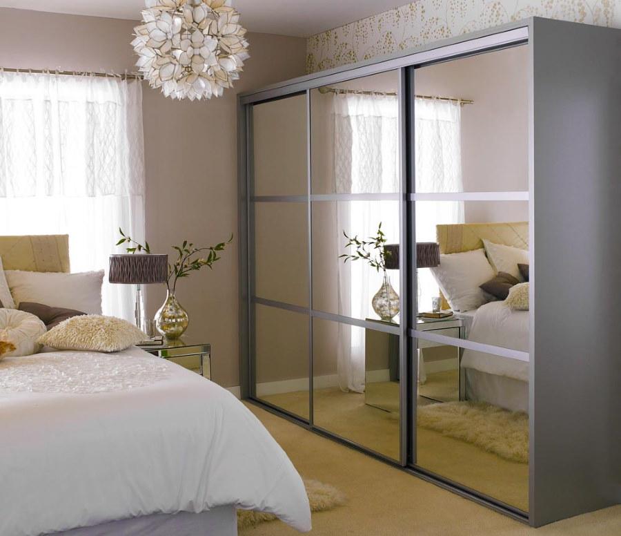 Зеркала на дверях серого шкафа в спальне