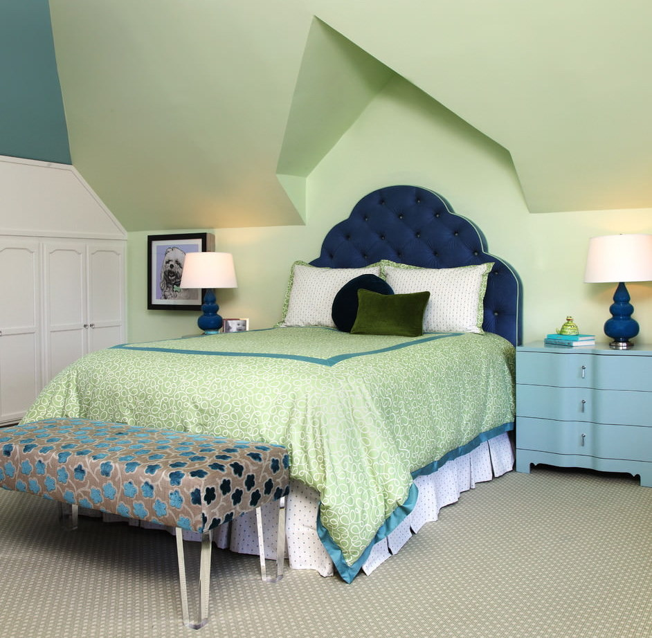 Синее изголовье кровати в комнате с зелеными стенами
