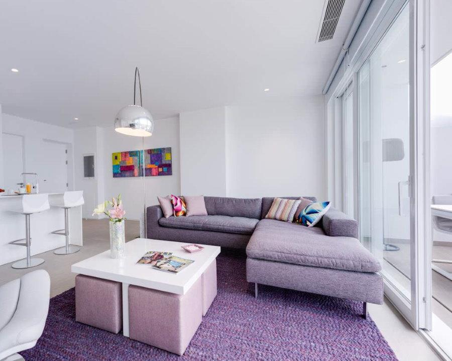 Сиреневый диван углового типа в гостиной с раздвижным окном