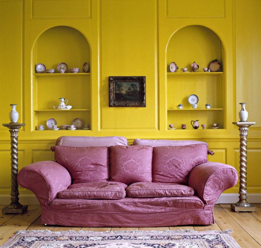 Светло-фиолетовый диван около ярко-желтой стены