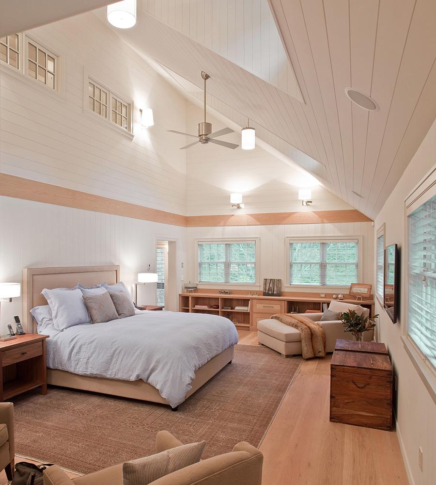 Крашенные доски светлого оттенка на потолке спальни
