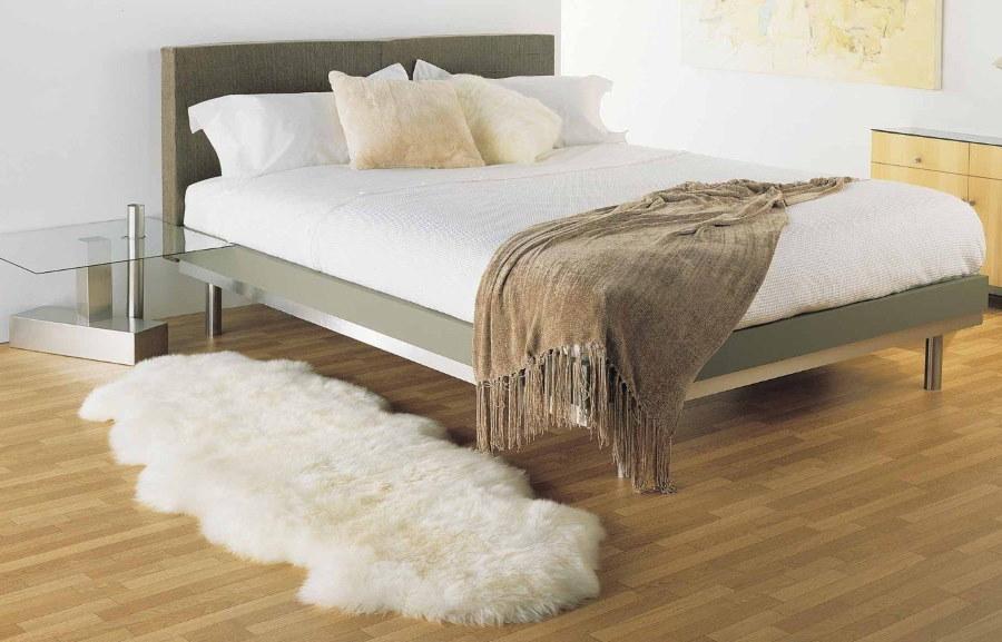 Пушистый коврик белого цвета перед кроватью
