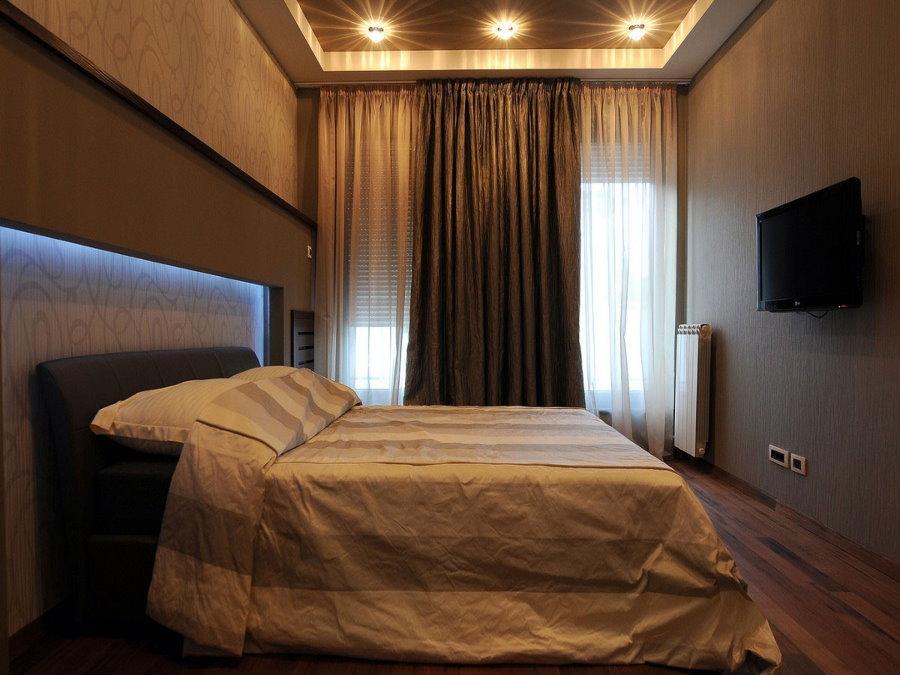 Узкая спальная комната с коричневыми стенами