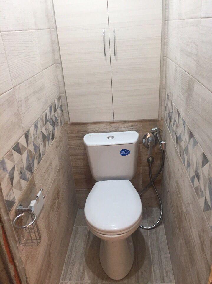 Шкаф для бытовых нужд за унитазом в узком туалете
