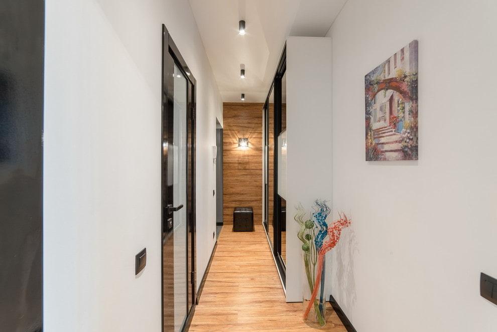 Узкий шкаф в длинном коридоре с белыми стенами