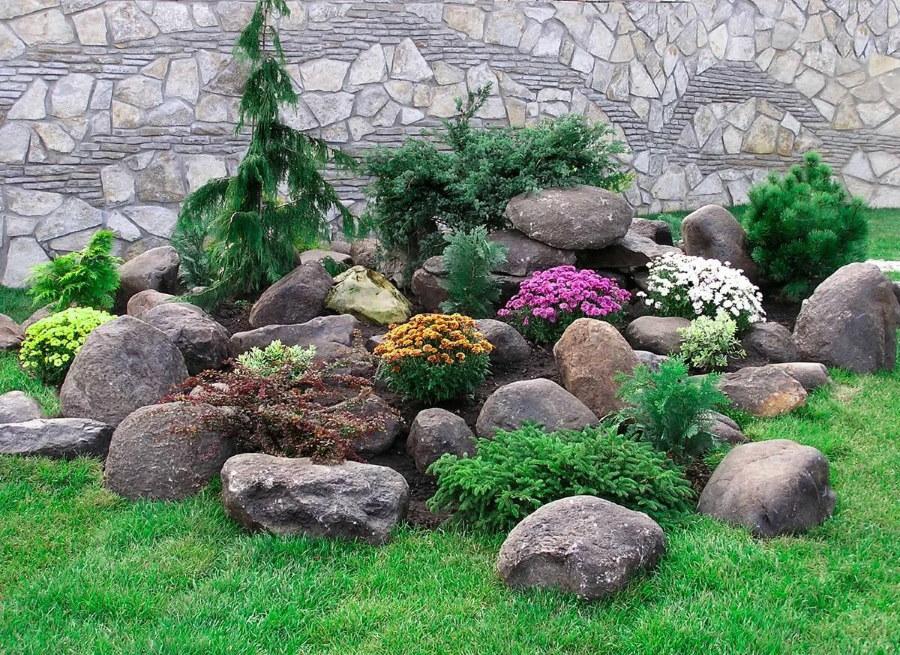 Природные камни на альпийской горке с цветами