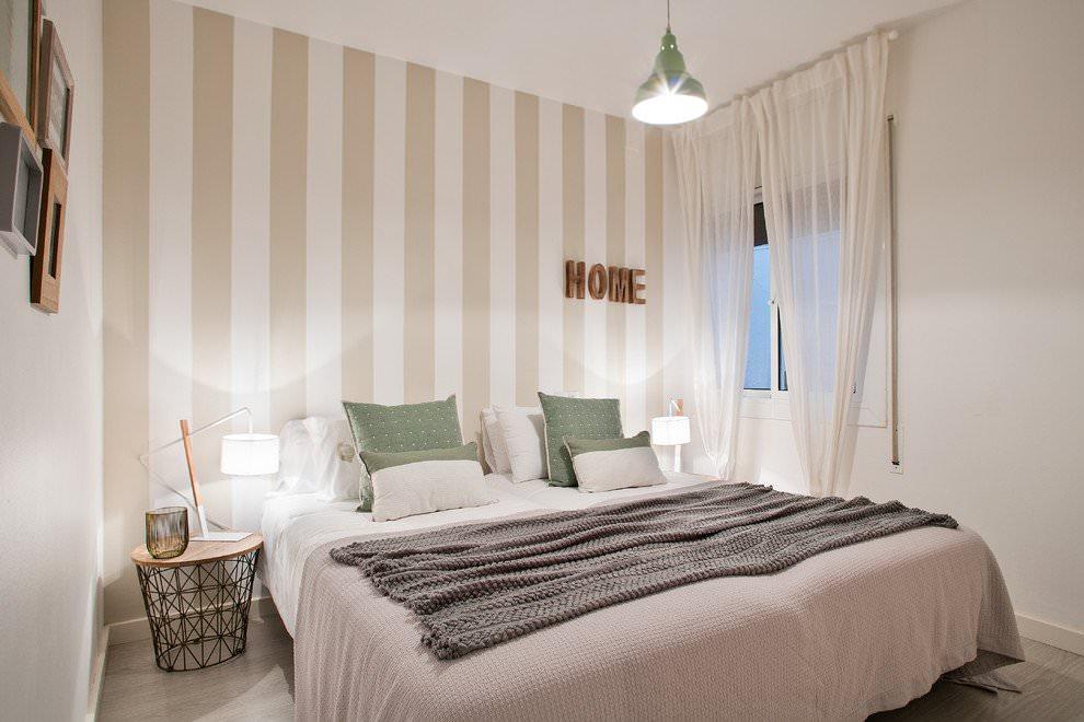 Светлая спальня с вертикальным принтом на обоях