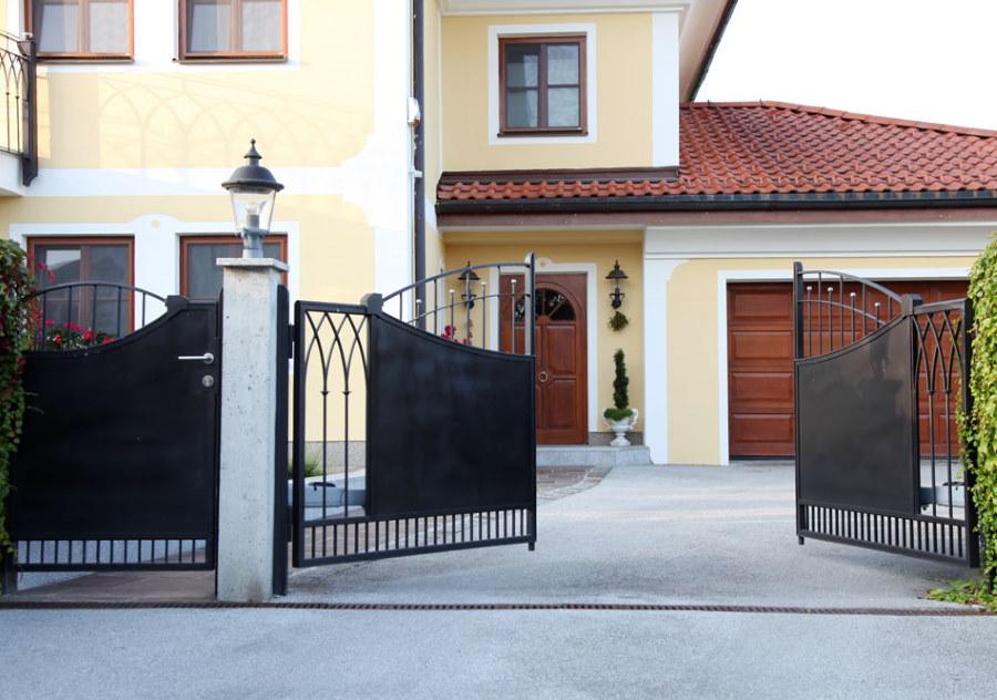 Открытые ворота во дворе двухэтажного дома