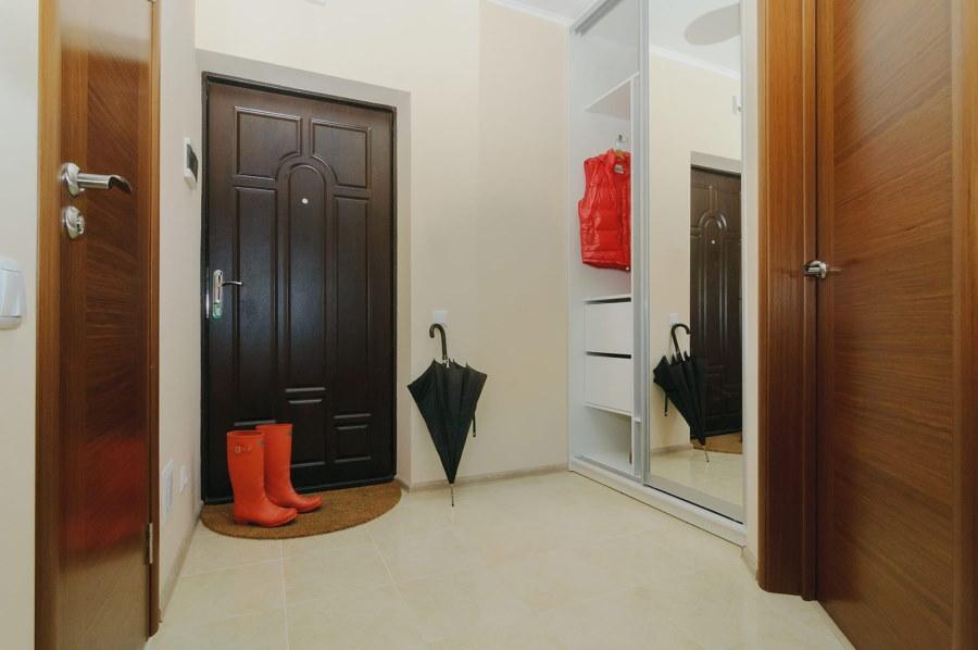 Черный зонт у двери в прихожей комнате