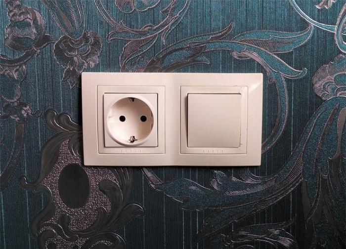 Блок с выключателем и розеткой на стене с обоями