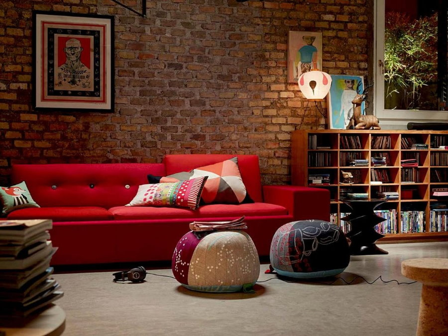 Красный диван в комнате с имитацией кирпичной стены