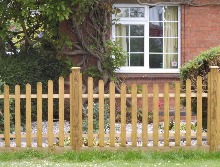 Деревянный забор перед кирпичным домом