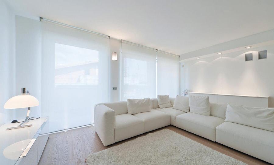 Угловой диван в гостиной с белыми шторами