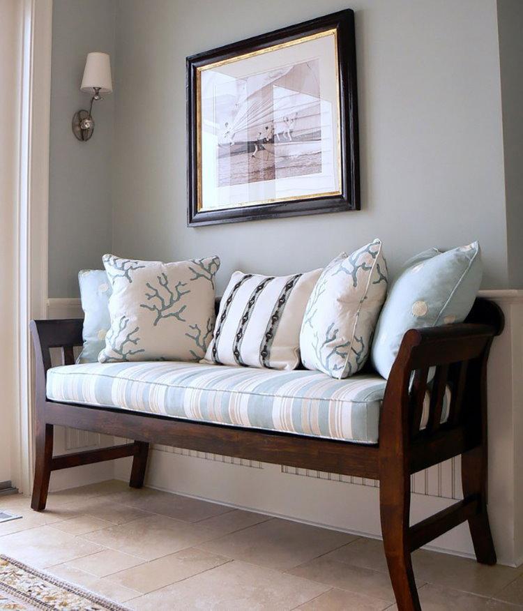 Деревянная скамья с удобными подушками вдоль стены коридора