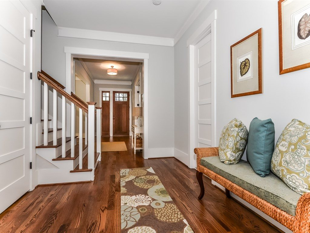 Стильная скамья с мягким сидением в холле с лестницей