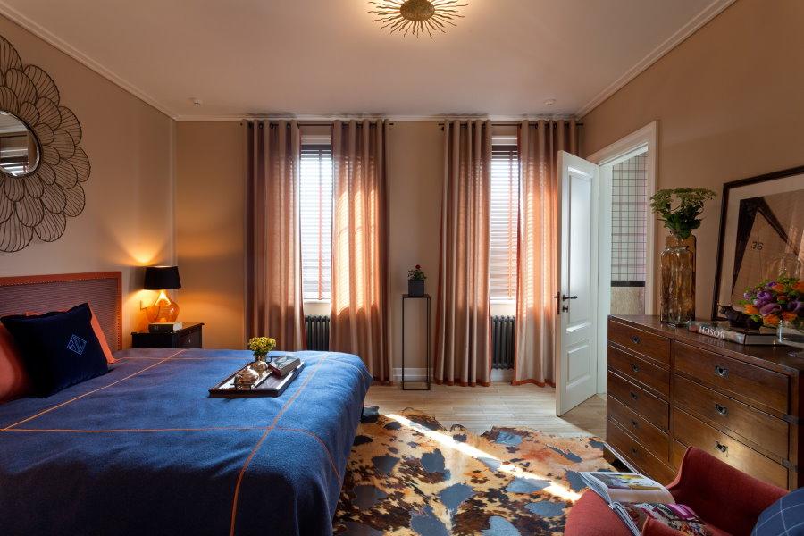 Широкий комод напротив двухспальной кровати в спальне супругов