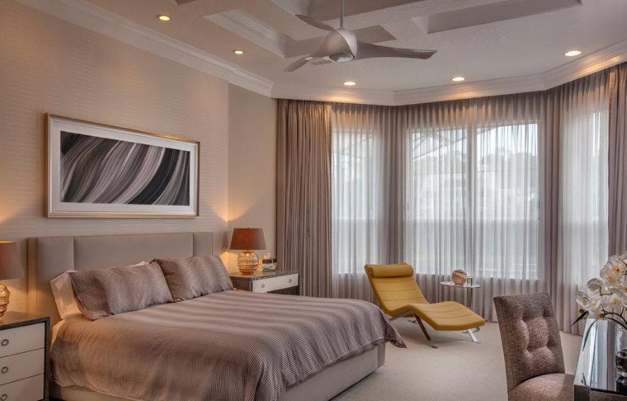 Интерьер большой спальни с окнами в эркере