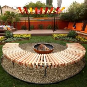 Скамейка из досок на площадке для отдыха с кострищем