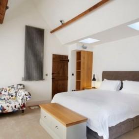 Деревянные балки на потолке спальни в мансарде