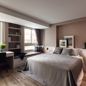 Интерьер большой спальной комнаты с двумя окнами