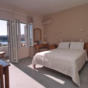 Серый ламинат на полу спальни с балконом