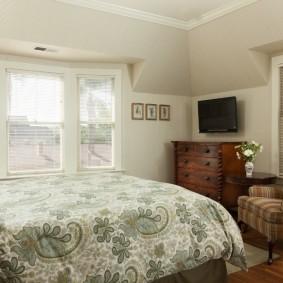 Деревянный комод между окнами в спальне