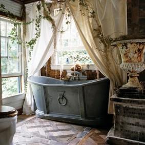 Серая ванна перед окном в загородном доме
