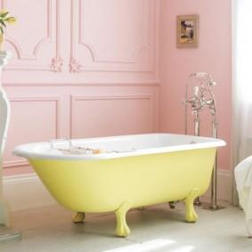 Желтая ванна на фоне розовых стен