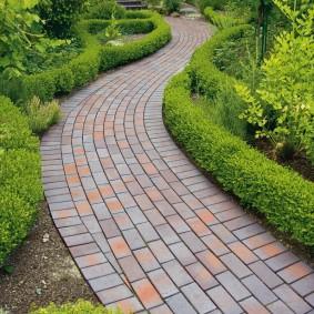 Тротуарная плитка на дорожке в саду регулярного стиля