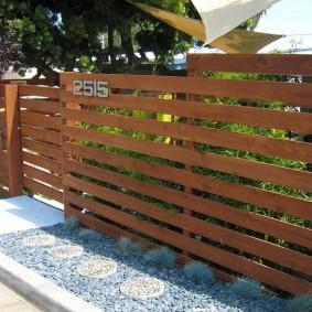 Горизонтально расположение доски на заборе перед домом