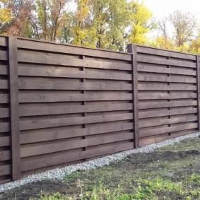Длинный забор из горизонтально закрепленных досок