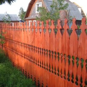 Забор с ручной резьбой возле частного дома