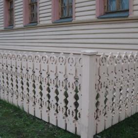 Резной забор перед домом с красивым фасадом