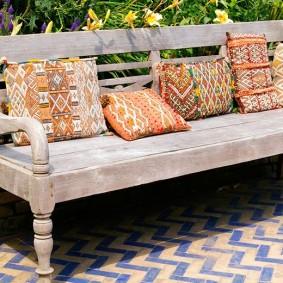 Пестрые подушки на скамейке с фигурными элементами