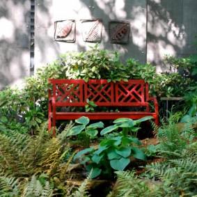 Красная скамейка в глубине сада