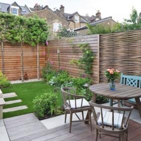 Садовая мебель на участке с плетенной оградой
