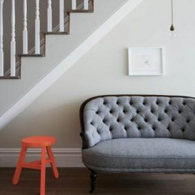 Мягкий диванчик под лестницей в холле