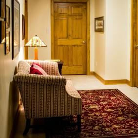 Мягкое кресло в коридоре с деревянными дверями