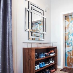 Зеркало в оригинальной раме на стене в прихожей