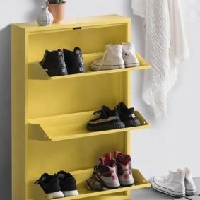 Желтая обувница около белой стены